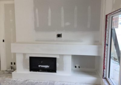unfinished drywall with fireplace
